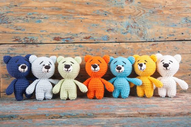 Veelkleurige gebreide kleine beer op een oude houten achtergrond. handgemaakt, gebreid speeltje. amigurumi