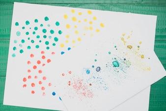 Veelkleurige gekleurd abstracte schilderkunst op wit papier over groene tafel