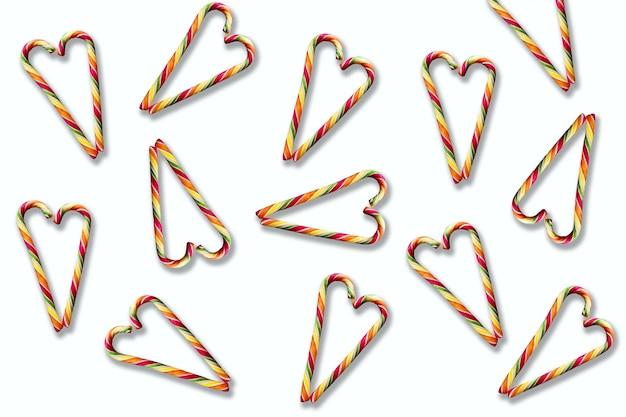 Veelkleurige gestreepte hartvormige lollies op een witte achtergrond. kerstmis, nieuwjaar, valentijnsdag, wintervakantiesfeer voor geliefden
