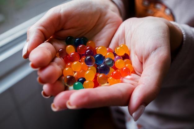 Veelkleurige glazen bollen in hun handen