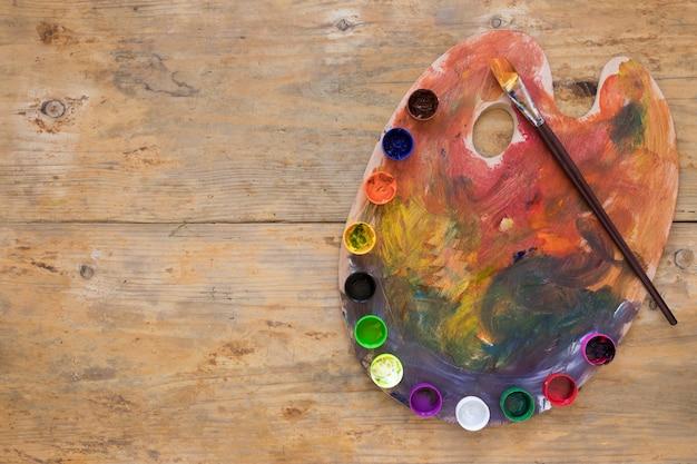 Veelkleurige gouache geplaatst op palet met kwast