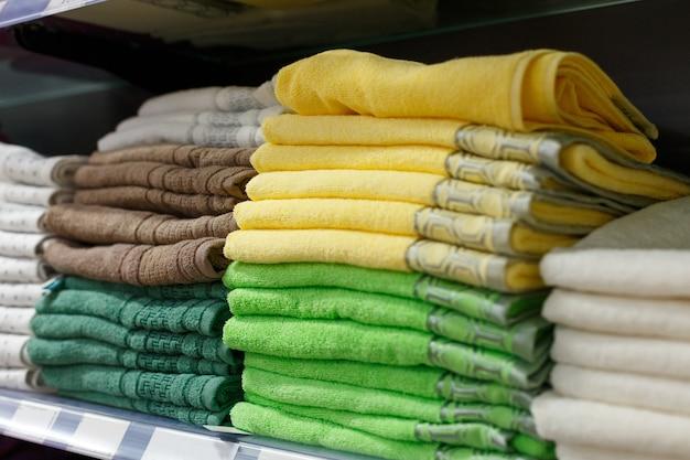 Veelkleurige handdoeken in stapels op de plank in de winkel, textielgedeelte in de winkel