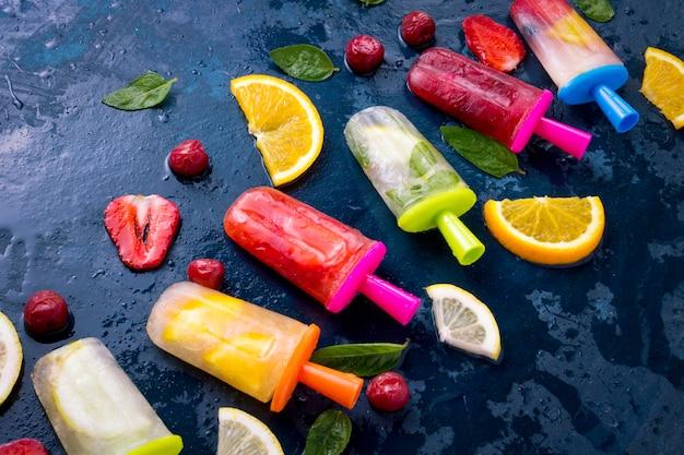 Veelkleurige helder fruit ijslolly met aardbei, kers, citroen, sinaasappel, citroen en munt en plakjes vers fruit op een donkerblauwe ondergrond