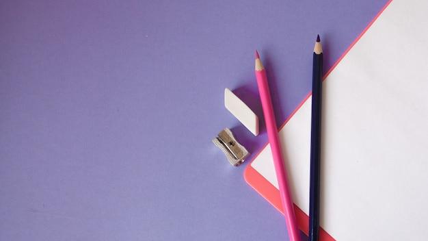 Veelkleurige, heldere, kleurrijke potloden bevinden zich onder een hoek en een notitieblok op een violette achtergrond