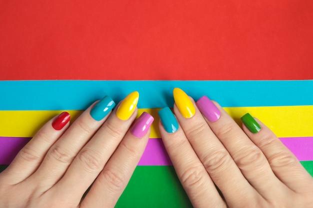 Veelkleurige heldere manicure met verschillende vormen van vierkante, ovale, scherpe nagels op een gekleurde achtergrond.