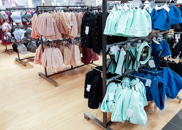 Veelkleurige hoeden en sjaals hangen in de winkel. korting en winkelconcept