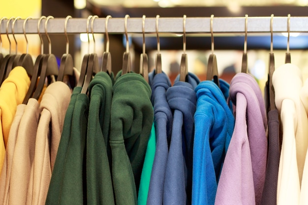 Veelkleurige hoodies op hangers in een sportwinkel