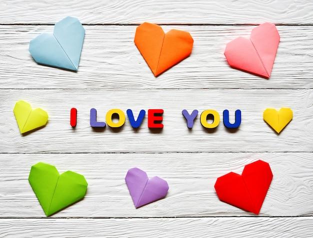 Veelkleurige houten letters die het opschrift i love you vormen en veelkleurige origami papieren harten op een witte houten valentijnsdag
