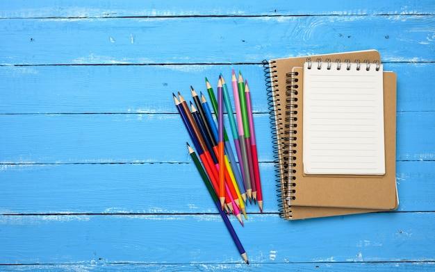 Veelkleurige houten potloden, lege spiraalvormige blocnotes op blauwe tafel, bovenaanzicht