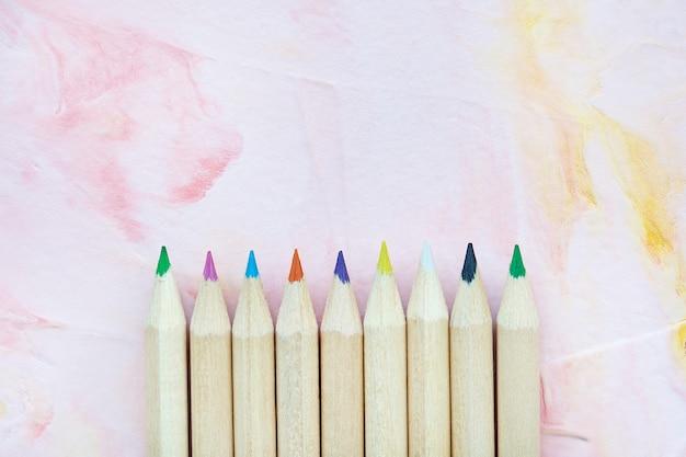 Veelkleurige houten potloden op roze achtergrond. tekenen, creatieve kunsten of terug naar school concept, kopieer ruimte