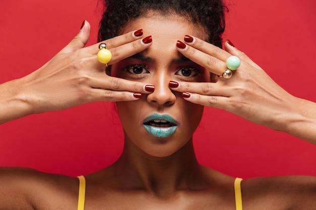 Veelkleurige jonge mulatvrouw die met trendy make-up op camera door vingers met ringen, over rode muur kijken