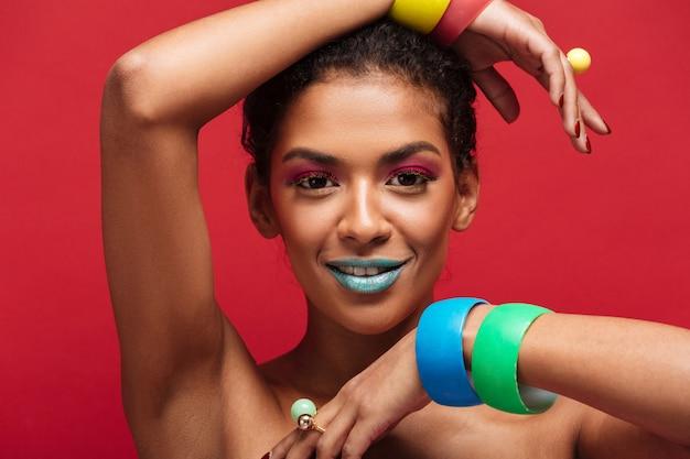 Veelkleurige jonge mulatvrouw die met trendy make-up op camera gesturing handen met armbanden, over rode muur kijken