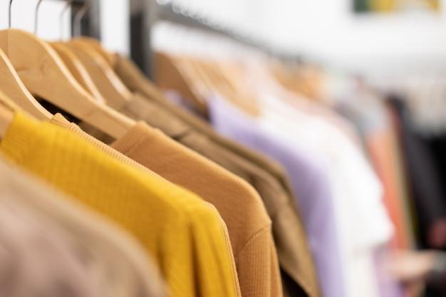 Veelkleurige kledingoverhemden hangen aan hangers. een verscheidenheid aan kleding hangt in de kledingkast. winkelen seizoen van vakantie te koop