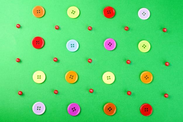 Veelkleurige knoppen en rode kralen op een groen oppervlak.