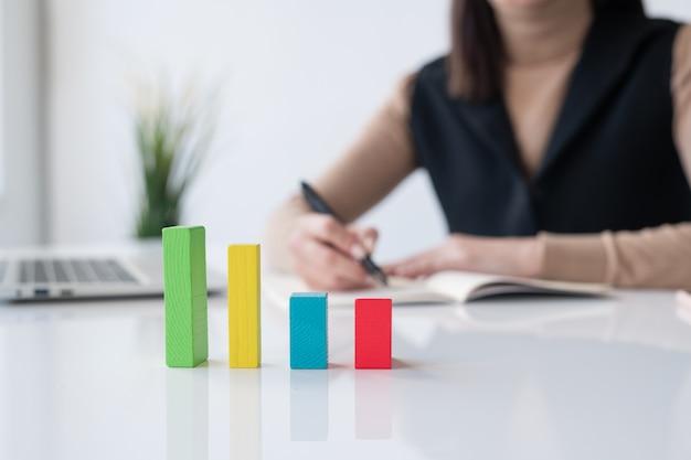 Veelkleurige kubusgrafiek op bureau op achtergrond van accountant of makelaar die financiële analyse in voorbeeldenboek opschrijven