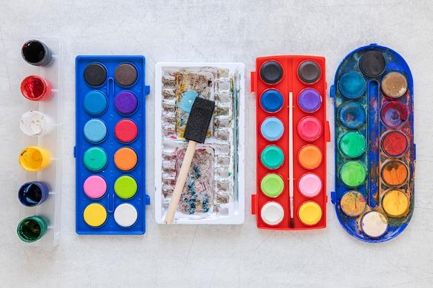 Veelkleurige kunstenaarspaletten in rode en blauwe containers