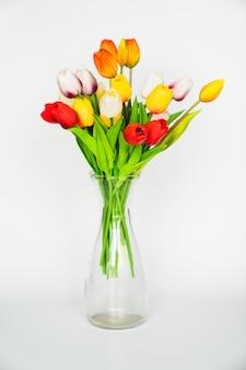 Veelkleurige kunstmatige tulpen in een transparante glazen vaas op een witte achtergrond. het interieur van het huis decoreren met planten. floristiek. verkoop van bloemen, planten en composities daarvan.