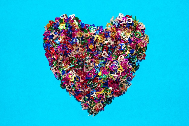 Veelkleurige letters van het engelse alfabet in de vorm van een hart op een blauw