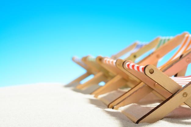 Veelkleurige ligstoelen op een rij op het zandstrand