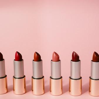 Veelkleurige lippenstiften staan op een rij. het concept van anders, collecties en schoonheid. rode, roze en bordeauxrode lippenstiften. verticaal