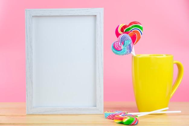 Veelkleurige lollies in een container op een roze achtergrond met kopie ruimte