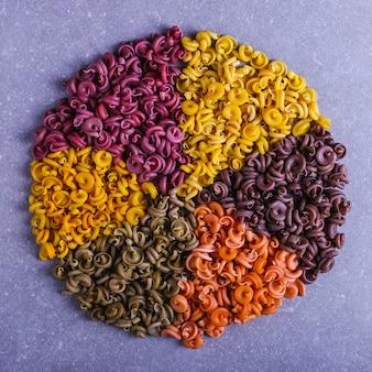 Veelkleurige macaroni van ongewone vorm met natuurlijke plantaardige kleurstoffen, gevoerd in een cirkel
