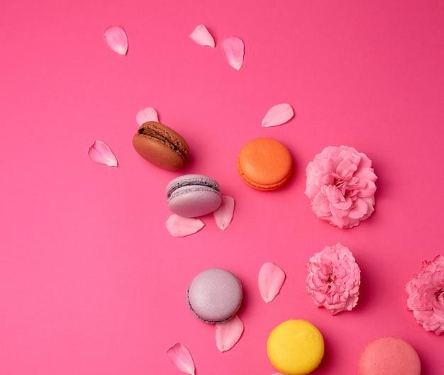 Veelkleurige macarons met crème en een roze rozenknop met verspreide bloemblaadjes