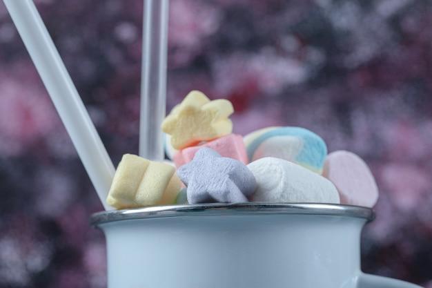 Veelkleurige marshmallows in een blauwe metalen beker.