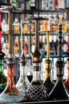 Veelkleurige mooie waterpijpen staan op de tafel op de achtergrond van alcohol aan de bar