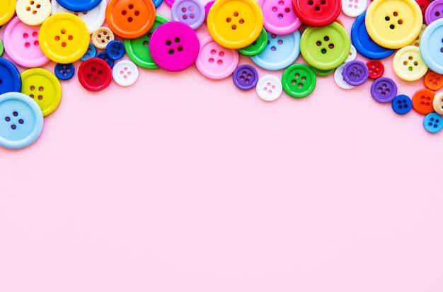 Veelkleurige naaien knoppen op een roze pastel achtergrond