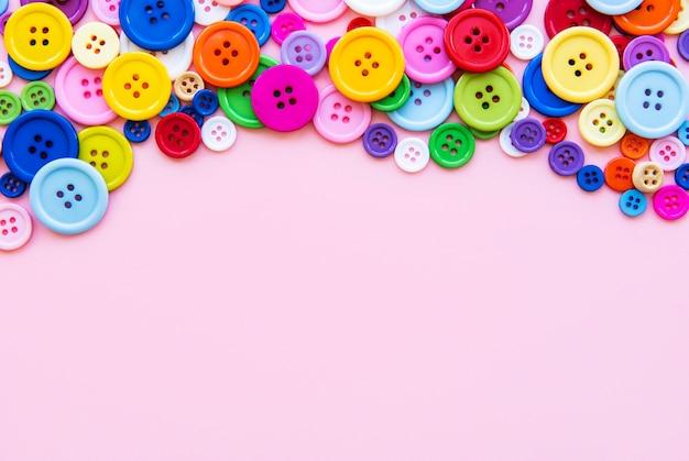 Veelkleurige naaien knoppen op een roze pastel oppervlak. rand naaien, bovenaanzicht