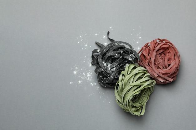 Veelkleurige ongekookte deegwaren met bloem op grijs