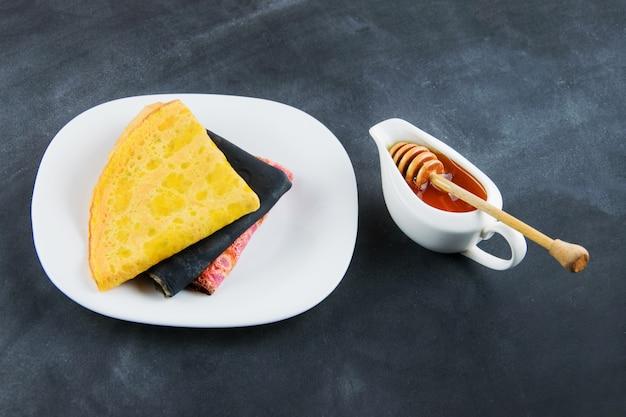 Veelkleurige pannenkoeken op witte plaat en honing op zwart