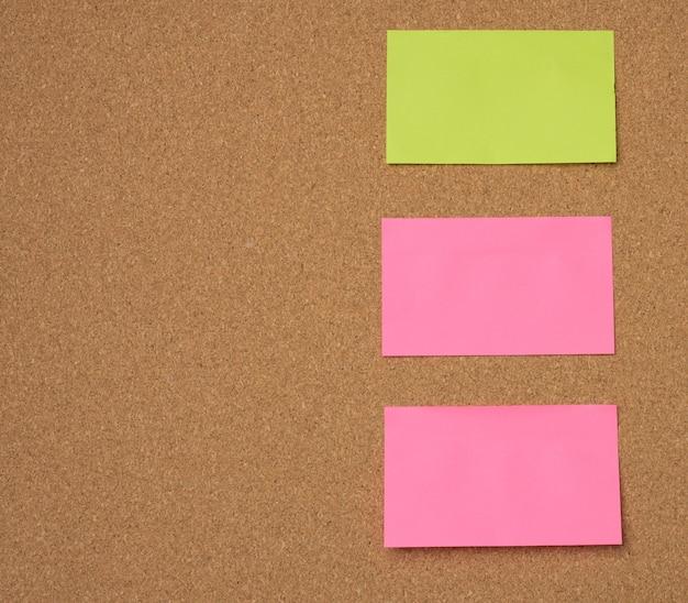 Veelkleurige papieren stokken zijn op het bruine kurkbord geplakt, kopieerruimte