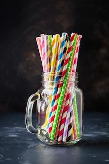 Veelkleurige papierrollen voor cocktail of rietjes in glazen pot op donkere achtergrond. selectieve aandacht.