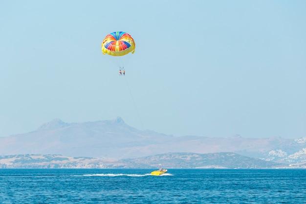 Veelkleurige parasailvleugel getrokken door een boot. zomerrecreatie op zee - bodrum, turkije.