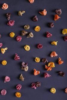 Veelkleurige pasta met de toevoeging van natuurlijke plantaardige kleurstof verspreid op een zwarte achtergrond. bovenaanzicht, patroon.