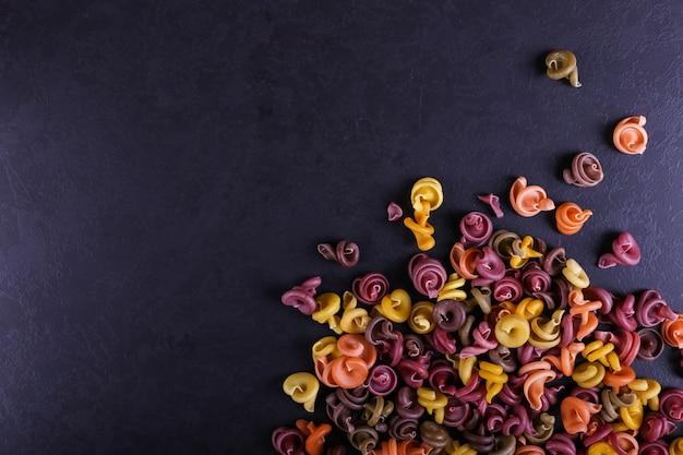 Veelkleurige pasta met de toevoeging van natuurlijke plantaardige kleurstof verspreid over een zwarte betonnen tafel. bovenaanzicht,.