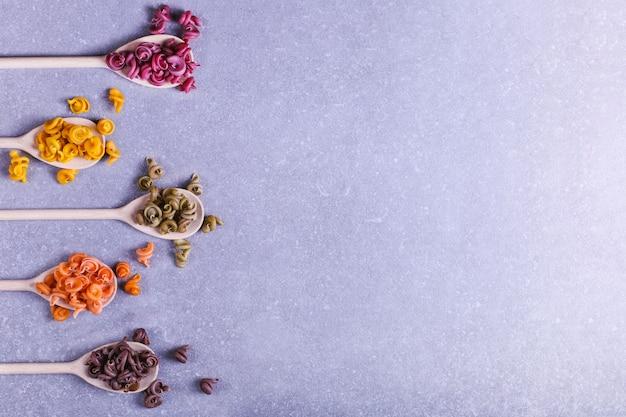 Veelkleurige pasta van ongebruikelijke vorm met natuurlijke plantaardige kleurstoffen, op houten lepels