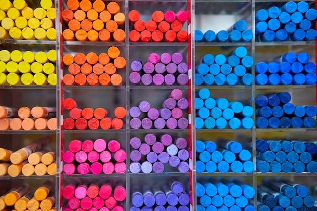 Veelkleurige pastel kleurpotloden kunstwinkel in houten cellen. artspace, workshop, creativiteitsconcept. moderne kunst. stijl abstracte achtergrond