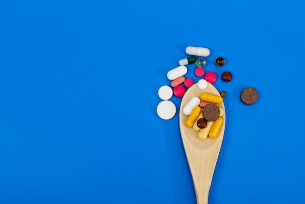 Veelkleurige pillen in een houten lepel