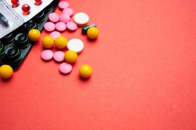 Veelkleurige pillen op rode achtergrond bovenaanzicht gezondheidsgeneesmiddelen