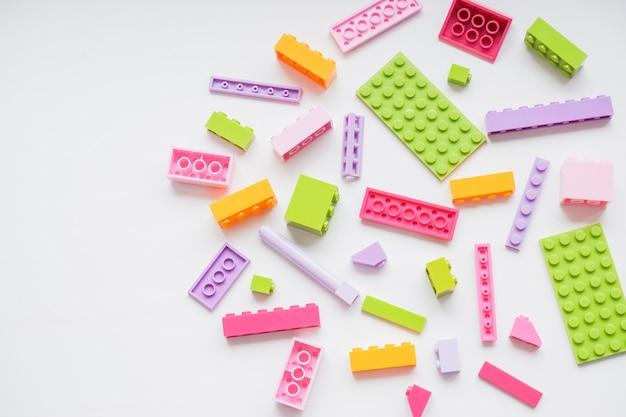 Veelkleurige plastic bouwstenen. delen van heldere kleine reserveonderdelen voor speelgoed.