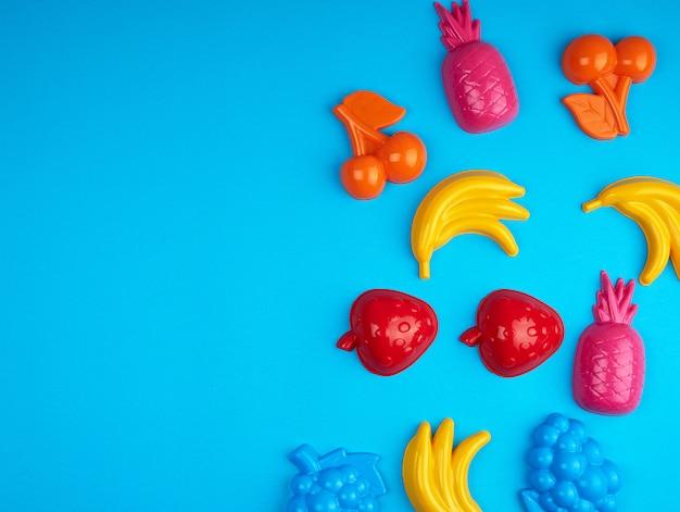 Veelkleurige plastic speelgoedvruchten op een blauwe achtergrond