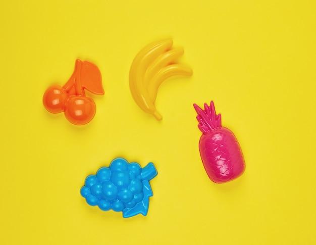 Veelkleurige plastic speelgoedvruchten op een geel