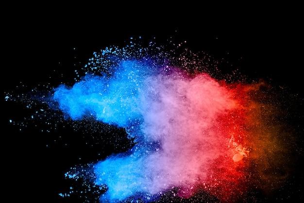 Veelkleurige poederexplosie op zwarte achtergrond. blauw roze en oranje stof spatten.