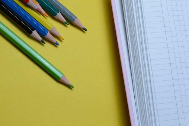 Veelkleurige potloden en een open notitieboekje liggen op een gele achtergrond. detailopname.