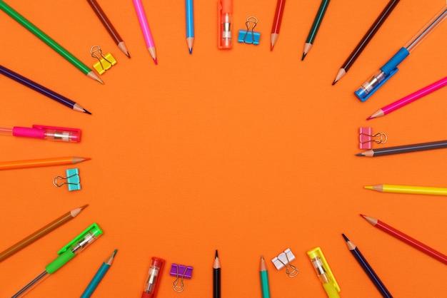 Veelkleurige potloden en pennen vormen een gekleurde cirkel geïsoleerd op een oranje achtergrond