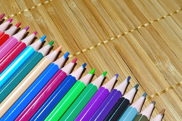 Veelkleurige potloden gerangschikt in een rij op een houten achtergrond.