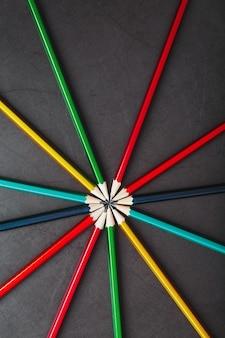 Veelkleurige potloden in de vorm van een ster op een zwarte achtergrond.